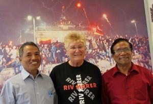 Dr Kem Thang, Helga Arntzen og U Bung Kone foran bildet av ville gledesscener i Berlin da muren falt.